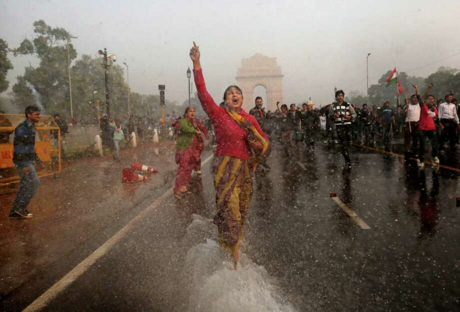 A female protester shouts as she is hit with an Indian police water cannon during a violent demonstration near the India Gate against a gang rape and brutal beating of a 23-year-old student on a bus last week, in New Delhi, India, Sunday. The attack last Sunday has sparked days of protests across the country. Photo: AP