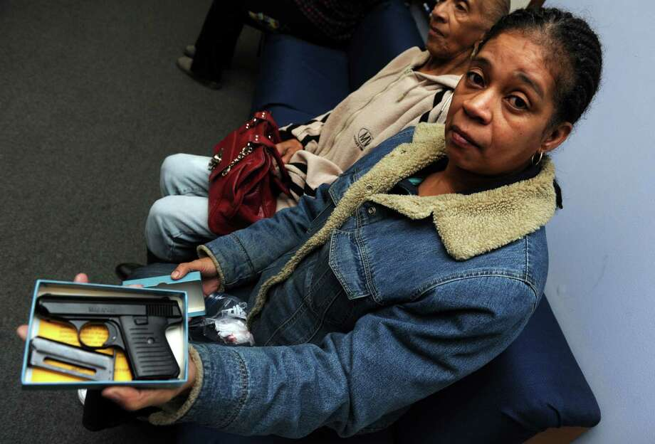 Debra Porter, of Bridgeport, waits to turn in a small handgun during a gun buyback event at the Bridgeport Police Department's Community Services Division Saturday in Bridgeport, Conn. In the wake of the tragedy in Newtown, Conn., the city raised $100,000 for the program and will offer up to $200 value for a working handgun, $75 for rifles and higher amounts for assault-type rifles.  Photo: AP