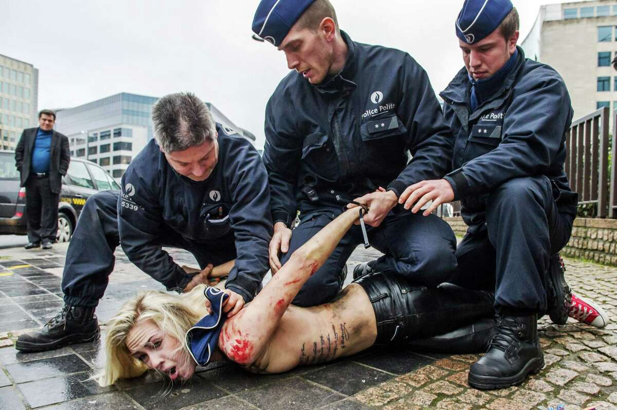 An activist of the Ukrainian movement Femen is arrested after she protested in front of the European Council building shouting Russia's President Putin is the Apocalypse, during the EU-Russia summit, in Brussels, Friday.