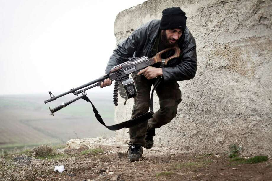 In this photo taken on Monday, a Free Syrian Army fighter takes cover during fighting with the Syrian Army in Azaz, Syria. Photo: AP