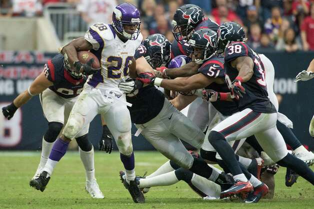Minnesota Vikings running back Adrian Peterson (28) is brought down by six different Houston Texans defenders during the fourth quarter at Reliant Stadium on Sunday, Dec. 23, 2012, in Houston. Photo: Smiley N. Pool, Houston Chronicle / © 2012  Houston Chronicle