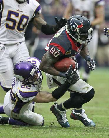 Houston Texans wide receiver Andre Johnson (80) readies him self for a hit as Minnesota Vikings free safety Harrison Smith (22) tries to wrap him up during the fourth quarter of a NFL game, Sunday, Dec. 23, 2012, at Reliant Stadium  in Houston. Photo: Nick De La Torre, Houston Chronicle / © 2012  Houston Chronicle