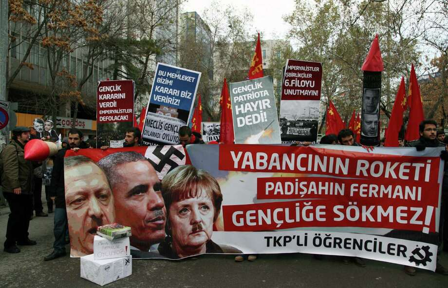 "Turkish students hold a poster with photos of Turkish Prime Minister Recep Tayyip Erdogan, left, US President Barack Obama, center, and German Chancellor Angela Merkel, made to look like Adolf Hitler, during a protest against the Turkish government and NATO's deployment of Patriot missiles near Turkey-Syria border, in Ankara, Turkey, Friday. The banner reads: "" The students will not obey before foreigners' rocket and Sultan's decree! "" Photo: AP"
