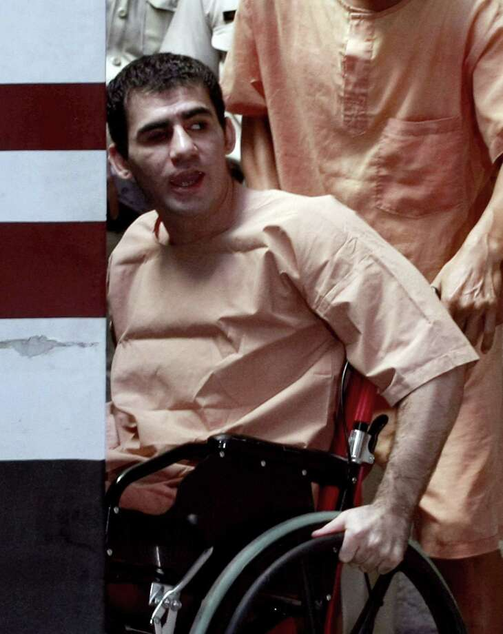 Saeid Moradi, an Iranian suspect bomber, on a wheelchair is helped by a Thai prisoner to arrive for his trial hearing at criminal court in Bangkok, Thailand, Friday. Moradi was wounded with his own bomb after it exploded when he hurled it to a group of chasing Thai police officers. He and compatriot Mohammad Kharzei were detained in Bangkok while another Iranian Masoud Sedaghatzadeh has been arrested in Malaysia after the series of explosion that occurred last February which wounded four other people. Photo: AP