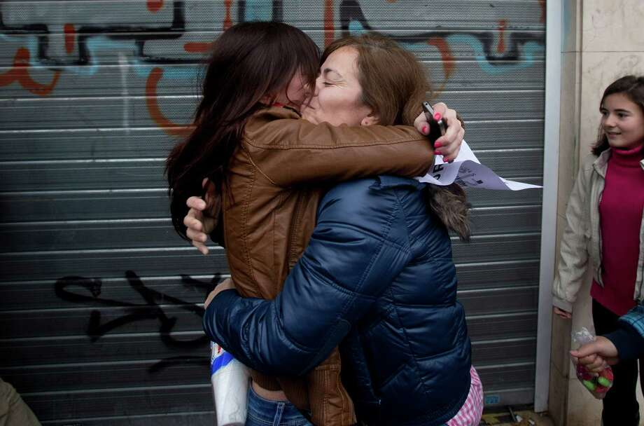 "Carmen, centre right hugs her daughter Azahara after winning part of the main Christmas lottery prize ""El Gordo"" (""The Fat One"") in Alcala de Henares, just outside of Madrid,  Saturday. Lucky winners of Spain's cherished Christmas lottery, the world's richest,  celebrated hitting ""El Gordo"" Saturday in more than a dozen locations across the country where winning tickets had been sold. Initial reports said there are winners of the maximum prize of euro 400,000 ($529,840) in 15 towns or cities including Madrid and Barcelona. Unlike lotteries that generate a few big winners, Spain's version, now celebrating its 200th anniversary, has always shared the wealth more evenly instead of concentrating on vast jackpots, so thousands of tickets yield some kind of return. Photo: AP"