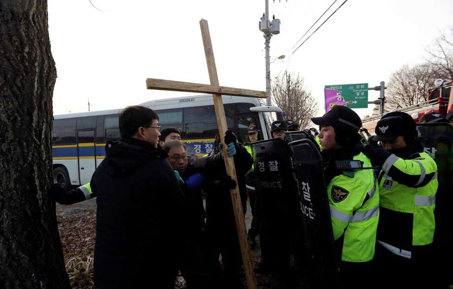 Local residents, second from left, is blocked by police officers as he tries to block Christian groups which light a 30-meter-tall (100-foot-tall) steel Christmas tree with about 30,000 light bulbs that would be visible by North Koreans living near the Demilitarized Zone dividing the two Koreas, near the western mountain peak known as Aegibong in Gimpo, South Korea, Saturday. Photo: AP