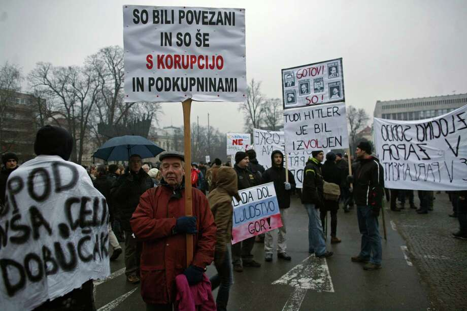 Slovenian protestors attend an anti-government rally in front of the parliament building in Ljubljana, Slovenia Friday. Several thousand protestors gathered in the Slovenian capital to demand better living conditions. Poster in center reads: Hitler also was elected. Banner at left reads : They have been  connected to corruption and they still are. Photo: AP