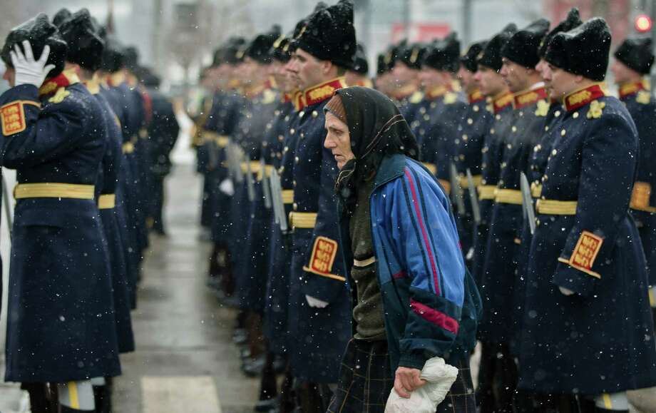 An elderly woman passes by honor guard soldiers standing during the commemoration of the 1989 anti-communist uprising at the Heroes Cemetery in Bucharest, Romania, Friday. The uprising, which left more than 1.000 dead, ended the rule of dictator Nicolae Ceausescu, 23 years ago. Revolution fighters and relatives of the dead ones scuffled briefly with riot police when they tried to prevent the laying of wreaths on behalf of the country's president and government . Photo: AP