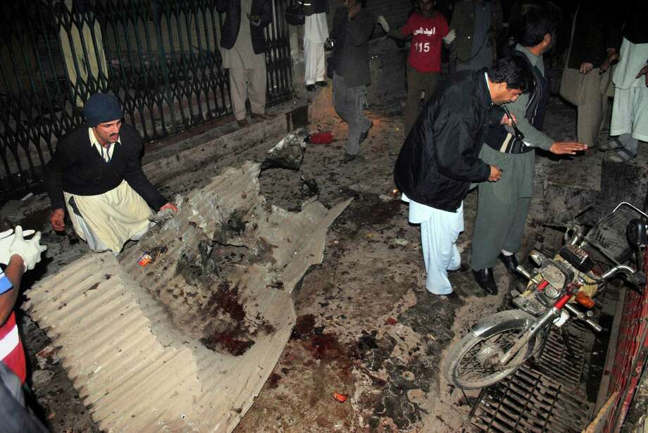 Pakistani plainclothes police officers and local residents examine at the site of a suicide bombing in Peshawar, Pakistan, Saturday. A suicide bomber in Pakistan killed several people including a provincial government official at a political rally held Saturday by a party that has opposed the Taliban, officials said. Photo: AP