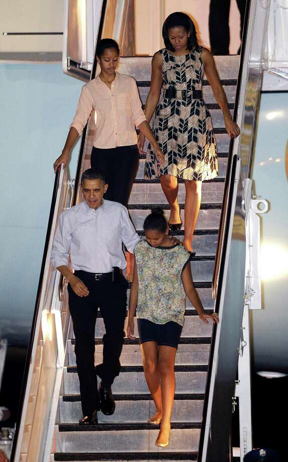President Barack Obama arrives with first lady Michelle Obama, top, and daughters Malia, top left, and Sasha, bottom right, at Honolulu Joint Base Pearl Harbor-Hickam in Honolulu, for the start of their holiday vacation, Saturday. Photo: AP