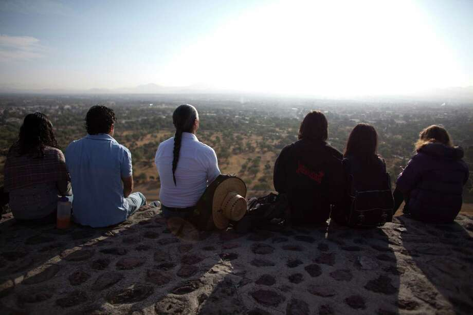 People meditate from the top of the Pyramid of the Sun at sunrise inside the Teotihuacan archeological site in Teotihuacan, Mexico, Friday. Many believe today is the conclusion of a vast, 5,125-year cycle in the Mayan calendar. Some have interpreted the prophetic moment as the end of the world, while others as believed it marked the birth of a new and better age. Photo: AP