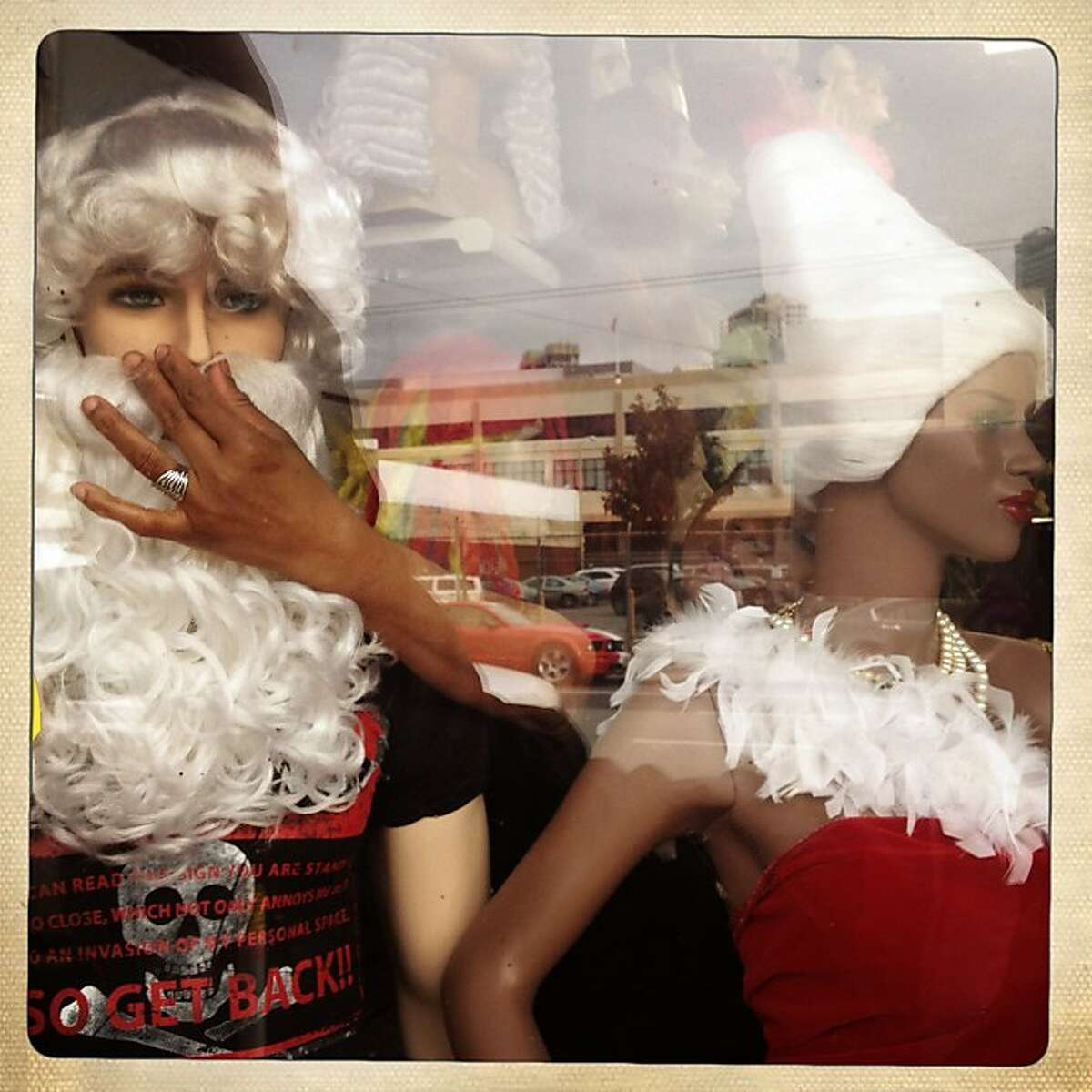 Beatrice Osunde adjusts a holiday display in the window of Trendy Hair Gallery and Beauty Supply on Thursday Dec. 21, 2012 in San Francisco, Calif.