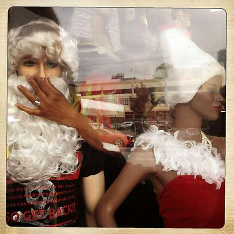 Beatrice Osunde adjusts a holiday display in the window of Trendy Hair Gallery and Beauty Supply in San Francisco. Photo: Mike Kepka, The Chronicle