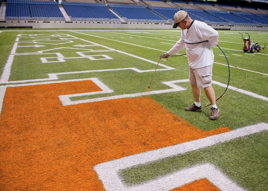Tom McAfee paints logos onto the field in preparation for the Alamo Bowl, Sunday, Dec. 23, 2012, at the Alamodome in San Antonio. Photo: Darren Abate, Darren Abate/For The Express-New