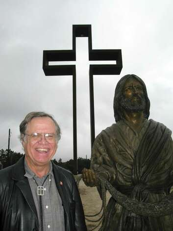 "Max Greiner Jr. designed ""The Empty Cross"" that stands atop the unfinished Coming King Sculpture Prayer Garden in Kerrville, as well as the sculpture shown here beside him. Dec. 3, 2012.  Money is slowly being raised to complete the garden, which Greiner would like to include paths lined by plaques with Bible verses, a visitors' center and museum, and a chapel. Photo: Zeke MacCormack, San Antonio Express-News / San Antonio Express-News"