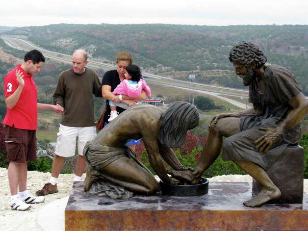 Luis Sosa (left) and his wife Yasmin, holding daughter Kaylee, pray with Chris Daniel beside a sculpture in the Coming King Sculpture Prayer Garden on a hill in Kerrville overlooking Interstate 10. Photo: Zeke MacCormack, San Antonio Express-News / San Antonio Express-News