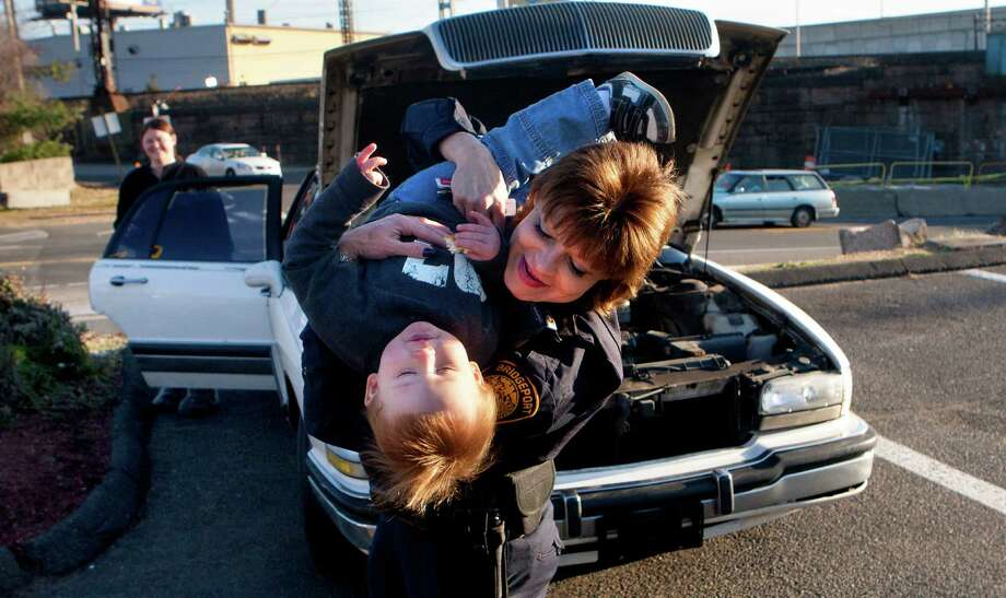 Amanda Arnold, left, watches as Bridgeport Police Sgt. Melody Pribesh plays with her 19-month-old son Kason Arnold after getting her car fixed Sunday, Dec. 23, 2012, in Bridgeport. Officers fixed Arnold's car after it broke down late Saturday night while Arnold was traveling to Florida. Bridgeport Police Sgt. Melody Pribesh allowed the two to stay with her overnight while police installed a new alternator and serpentine belt. She also went home with some extra cash after officers took up (Cody Duty / Hearst Newspapers ) Photo: Cody Duty, Cody Duty/Hearst Newspapers / The News-Times