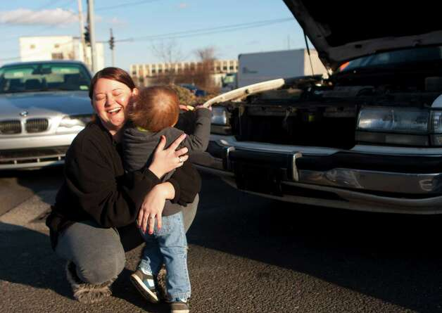 Amanda Arnold holds her 19-month-old son Kason Arnold after getting her car fixed Sunday, Dec. 23, 2012, in Bridgeport. Officers fixed Arnold's car after it broke down late Saturday night while Arnold was traveling to Florida. Bridgeport Police Sgt. Melody Pribesh allowed the two to stay with her overnight while police installed a new alternator and serpentine belt. She also went home with some extra cash after officers took up (Cody Duty / Hearst Newspapers ) Photo: Cody Duty, Cody Duty/Hearst Newspapers / The News-Times