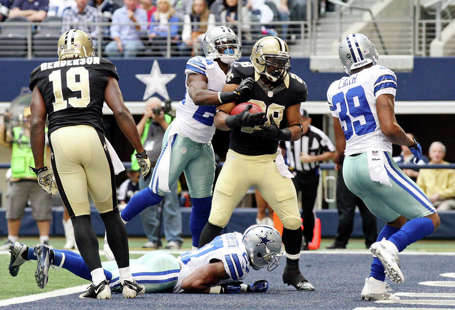 New Orleans Saints' Mark Ingram (center) scores a touchdown between Dallas Cowboys' Morris Claiborne (from left) Eric Frampton (bottom), and Brandon Carr as New Orleans Saints' Devery Henderson looks on during first half action Sunday Dec. 23, 2012 at Cowboys Stadium in Arlington, Tx. Photo: Edward A. Ornelas, Express-News / © 2012 San Antonio Express-News