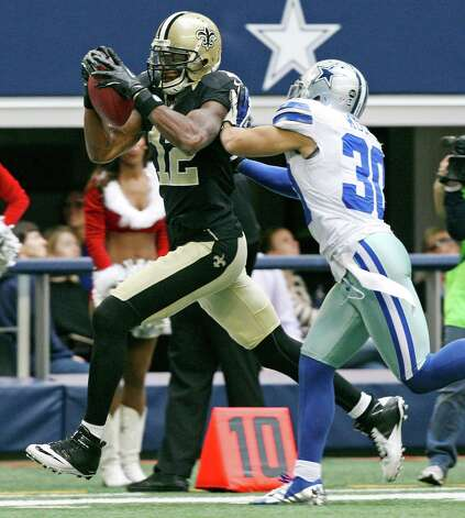 New Orleans Saints' Marques Colston is pushed out of bounds by Dallas Cowboys' Sterling Moore during second half  action Sunday Dec. 23, 2012 at Cowboys Stadium in Arlington, Tx. The Saints won in overtime 34-31. Photo: Edward A. Ornelas, Express-News / © 2012 San Antonio Express-News