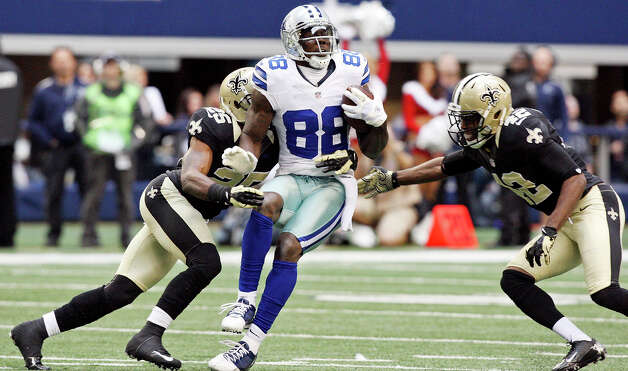 Dallas Cowboys' Dez Bryant looks for room between New Orleans Saints' Rafael Bush (left) and New Orleans Saints' Isa Abdul-Quddus  during second half action Sunday Dec. 23, 2012 at Cowboys Stadium in Arlington, Tx. The Saints won in overtime 34-31. Photo: Edward A. Ornelas, Express-News / © 2012 San Antonio Express-News