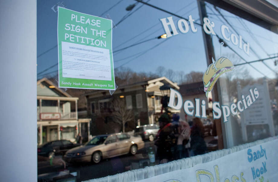 A sign asking people to sign an assault weapons ban petition is displayed in the window of Sandy Hook Deli & Catering on Sunday, December 23, 2012. Nearby Sandy Hook Elementary School was the scene of violence that killed 20 students and six staff members. Photo: Joshua Trujillo, Hearst Newspapers