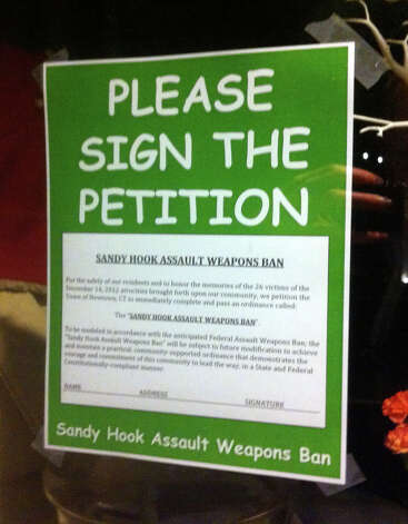This sign petitioning for a Newtown assault weapons ban was posted at Demitasse Cafe, which is a short walk from where 20 students and 6 teachers were shot to death at Sandy Hook Elementary School. The picture was taken Dec. 23, 2012. Photo: Casey McNerthney/Hearst Newspapers