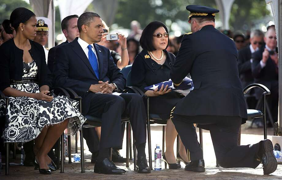 President Obama and first lady Michelle Obama watch as Irene Hirano Inouye, the widow of the late Sen. Daniel Inouye, receives the flag that was draped over her husband's casket during a memorial service at the National Memorial Cemetery of the Pacific in Honolulu. Several of Inouye's Senate colleagues were also in attendance. Photo: Carolyn Kaster, Associated Press