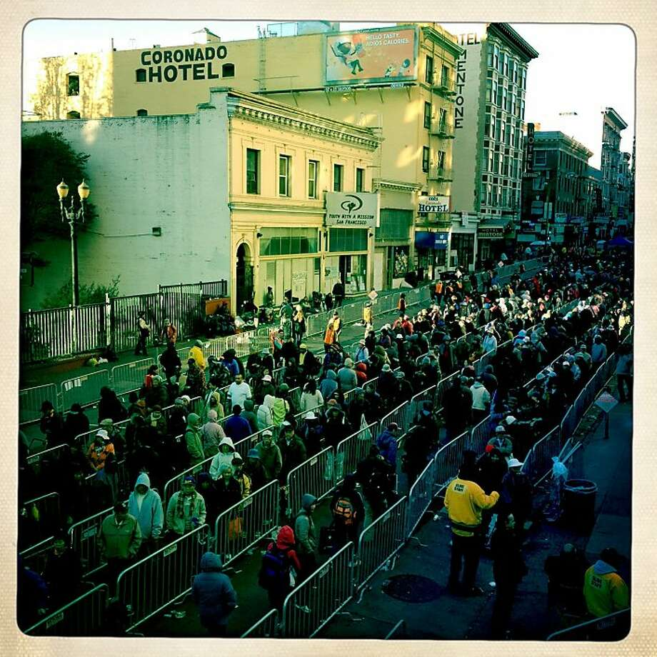 A long line of people snakes back and forth in front of Glide Memorial Church to receive a bag of holiday groceries in San Francisco, Calif. on Wednesday, Dec. 19, 2012. Photo: Paul Chinn, The Chronicle