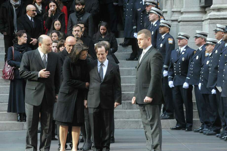 Madonna and Matthew Badger are flanked by the Stamford firefighters as they watch the caskets exit the funeral for the three Badger sisters, Lilian, Sarah and Grace, takes place at St. Thomas Church Fifth Avenue in Manhattan, N.Y., on Thursday, January 5, 2012. The sisters were killed along with their grandparents, Lomer and Pauline Johnson, when their mother's Shippan home burned down on Christmas Day. Photo: Keelin Daly / Stamford Advocate