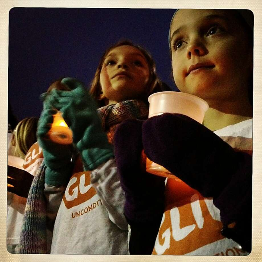 Alanna Martin, 7 years old  and Sarah Novick, 5 years old, wear their winter mittens as they hold candles during the singing performance, Thursday Dec. 20, 2012, at the  Holiday Ice Rink at the Embarcadero,  in San Francisco, Calif. Photo: Lacy Atkins, The Chronicle