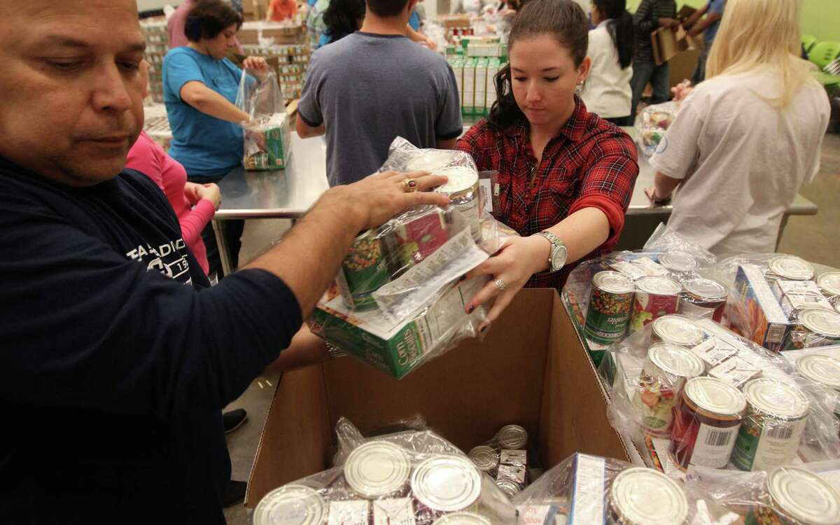 Volunteers Angel Carrion Jr. and Nicole Allen place prepared packs of food supplies into transportation bins to be distributed to needy children at the Houston Food Bank, which is struggling to keep its pantry full because of a decline in government donations.
