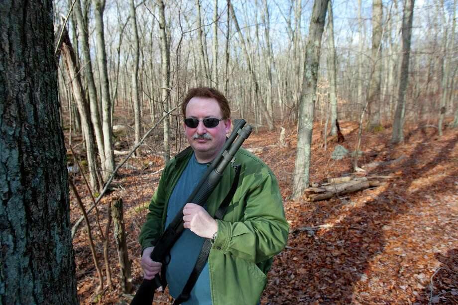 """Adam Palmer holds up a shotgun in the woods Sunday, Dec. 23, 2012, in Ansonia. Palmer believes in being prepared with the right tools in case events take place such as natural disasters. """"Every gun is a tool,"""" Palmer said. """"Like a shovel, every tool has its purpose."""" ( Cody Duty / Hearst Newspapers ) Photo: Cody Duty, Cody Duty/Hearst Newspapers / The News-Times"""