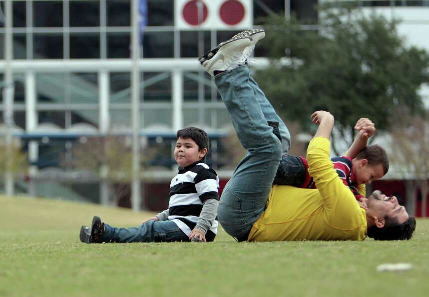 Rodolfo Ortiz right, plays with his two-year-old son Patricio Ortiz center, and four-year-old son Al