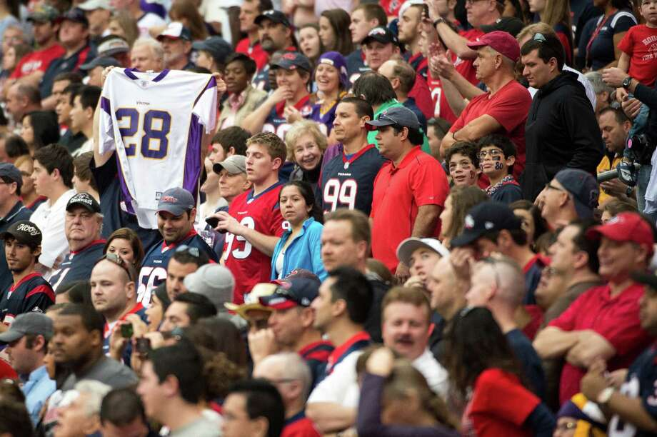 Fans hold up the jersey of Vikings running back Adrian Peterson during the first quarter. Photo: Smiley N. Pool, Houston Chronicle / © 2012  Houston Chronicle