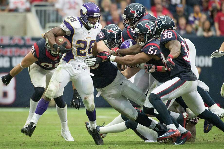 Vikings running back Adrian Peterson (28) is brought down by six different Houston Texans defenders during the fourth quarter. Photo: Smiley N. Pool, Houston Chronicle / © 2012  Houston Chronicle
