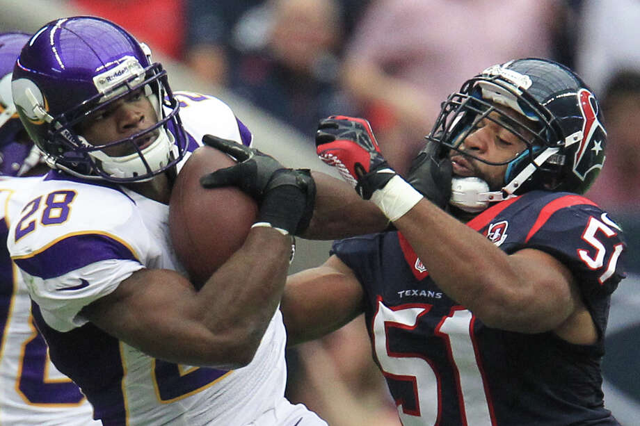 Vikings running back Adrian Peterson (28) is brought down by Texans inside linebacker Darryl Sharpton (51) during the first quarter. Photo: Karen Warren, Houston Chronicle / © 2012 Houston Chronicle