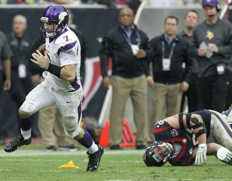 Vikings quarterback Christian Ponder (7) evades the tackle of Texans defensive end J.J. Watt (99) du
