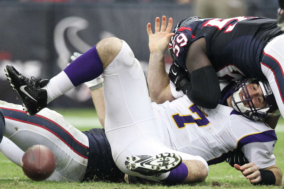 Vikings quarterback Christian Ponder (7) fumbles as he is hit by Texans linebacker Whitney Mercilus (59) and defensive end J.J. Watt (99) during the third quarter. Photo: Nick De La Torre, Houston Chronicle / © 2012  Houston Chronicle