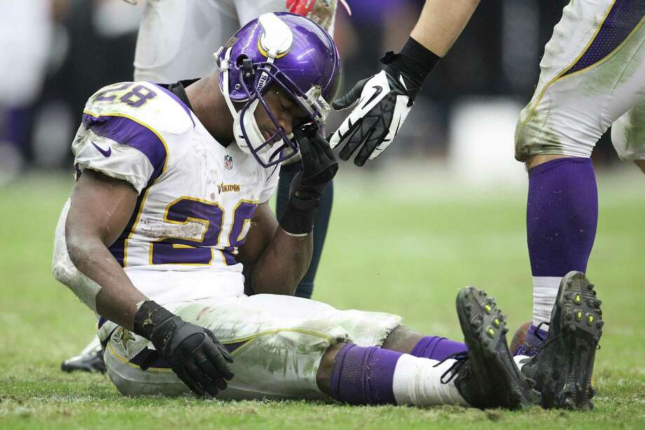 Vikings running back Adrian Peterson sits on the field picking grass out of his helmet during the third quarter. Photo: Karen Warren, Houston Chronicle / © 2012 Houston Chronicle