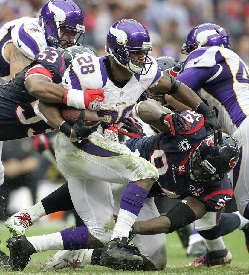 Vikings running back Adrian Peterson (28) is brought down by Texans inside linebacker Bradie James (53) and defensive end Antonio Smith (94) during the third quarter. Photo: Karen Warren, Houston Chronicle / © 2012 Houston Chronicle