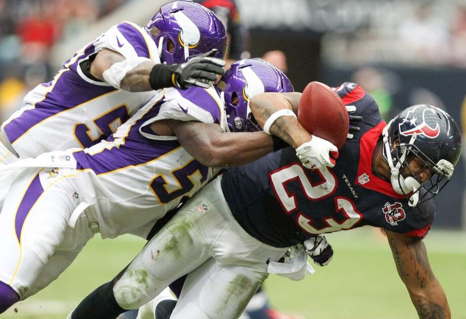 Texans running back Arian Foster (23) fumbles as he is hit by Vikings linebackers Jasper Brinkley (54) and Erin Henderson (50) for a turnover during the second quarter. (Nick de la Torre / Houston Chronicle)