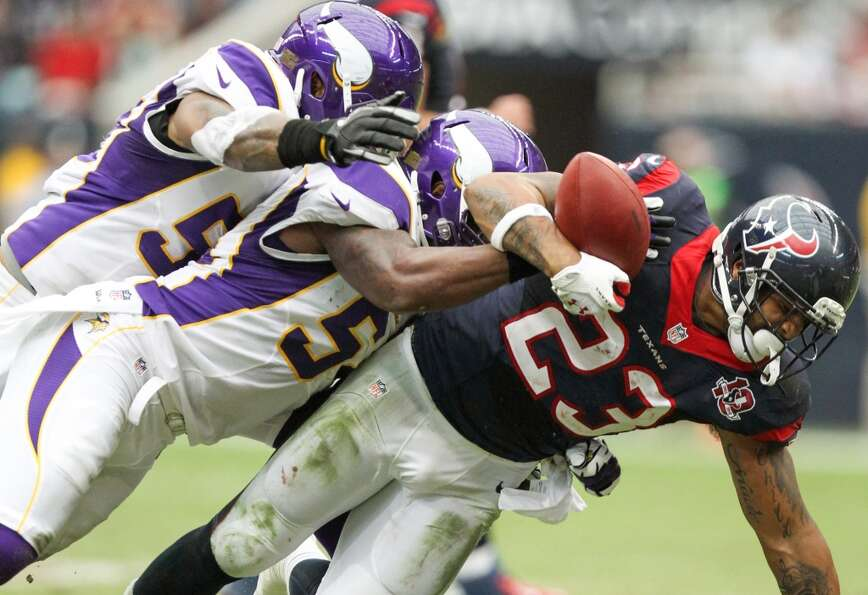 Texans running back Arian Foster (23) fumbles as he is hit by Vikings linebackers Jasper Brinkley (5