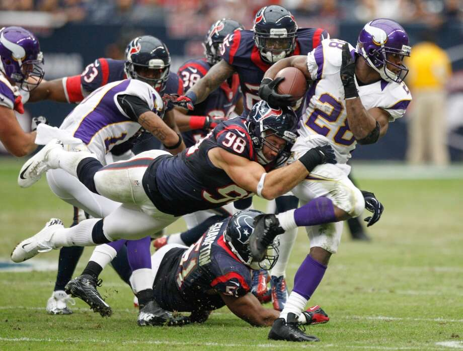 Texans linebacker Connor Barwin (98) tackles Vikings running back Adrian Peterson (28) during the second quarter. (Brett Coomer / Houston Chronicle)