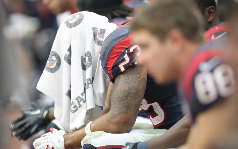 Texans running back Arian Foster (23) sits on the bench with a towel over his head during the third quarter. (Karen Warren / Houston Chronicle)