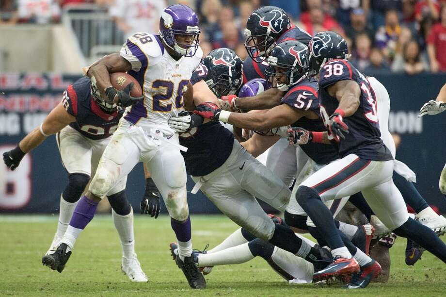Vikings running back Adrian Peterson (28) is brought down by six different Houston Texans defenders during the fourth quarter. (Smiley N. Pool / Houston Chronicle)