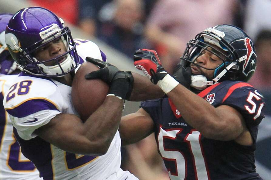 Vikings running back Adrian Peterson (28) is brought down by Texans inside linebacker Darryl Sharpto
