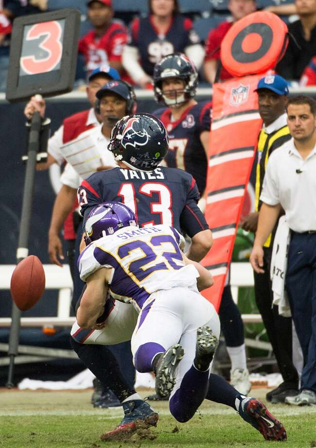 Texans quarterback T.J. Yates (13) fumbles as he is hit by Vikings free safety Harrison Smith (22) during the fourth quarter. (Smiley N. Pool / Houston Chronicle)