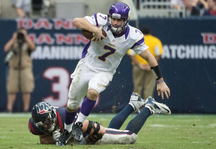 Vikings quarterback Christian Ponder (7) gets past Texans defensive end J.J. Watt (99) on a 29-yard scramble during the fourth quarter. (Smiley N. Pool / Houston Chronicle)