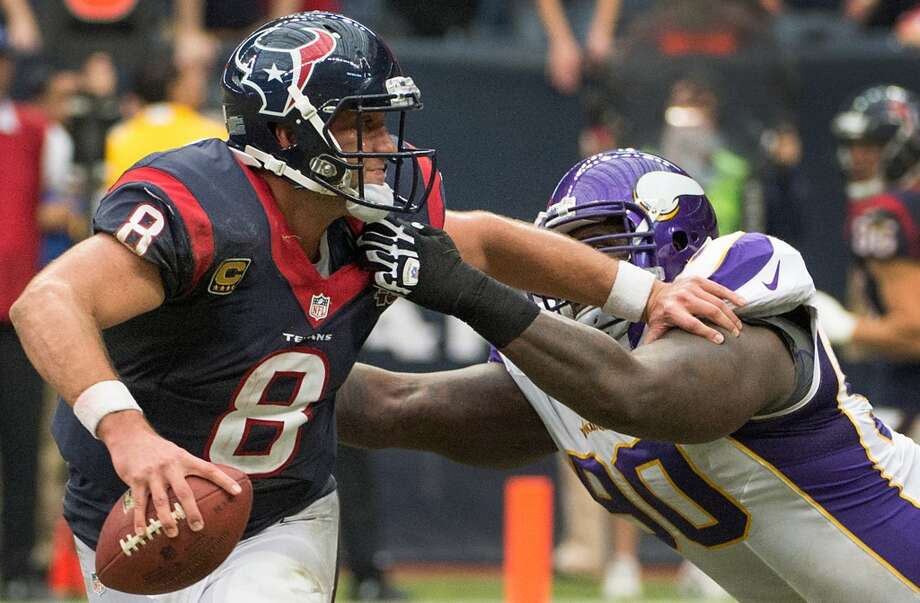 Vikings defensive tackle Fred Evans (90) drops Houston Texans quarterback Matt Schaub (8) for a 14-yard loss during the third quarter. (Smiley N. Pool / Houston Chronicle)